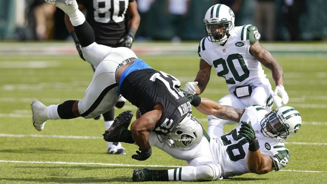 New York Jets strong safety Dawan Landry (26) tackles Oakland Raiders running back Maurice Jones-Drew (21) during the second half of an NFL football game Sunday, Sept. 7, 2014, in East Rutherford, N.J.