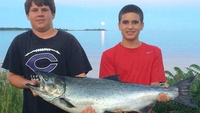 With a full moon rising behind them over Baileys Harbor, Mark (Joseph) Hahn Jr. of California (left) and his cousin, Eric Hahn of Missouri, showed off the winning fish in the 33rd annual K/D Salmon Tournament.