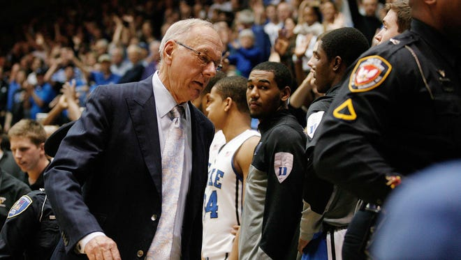Syracuse coach Jim Boeheim is escorted off the court after getting ejected from the game against Duke with 10.4 seconds left at Cameron Indoor Stadium.