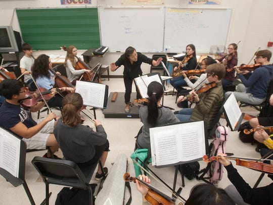Louisville Youth Orchestra music director and conductor Deanna Tham works with some of the orchestra's young musicians at the Youth Performing Arts School. The orchestra includes over 350 musicians from 60 schools and 15 counties from the Louisville and Southern Indiana metropolitan area.