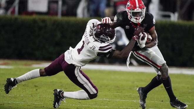 Mississippi State cornerback Martin Emerson, left, tackles Georgia wide receiver George Pickens during the first half of an NCAA college football game Saturday, Nov. 21, 2020, in Athens, Ga.