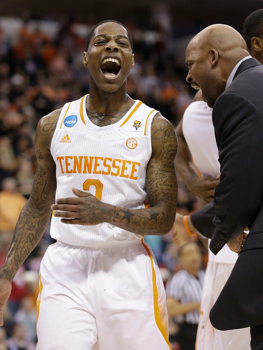 Tennessee guard Antonio Barton (2) celebrates with Tennessee head coach Cuonzo Martin near the the end of the first half of an NCAA college basketball third-round tournament game against Mercer, Sunday, March 23, 2014, in Raleigh. (AP Photo/Gerry Broome)