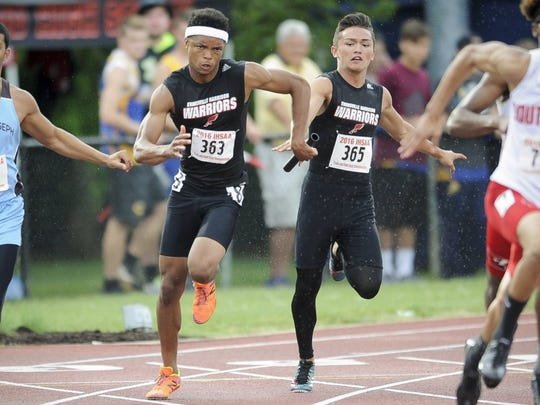 Harrison's Noah McBride (363) takes the baton from teammate Brian Nally (365) during the 400-meter relay during the IHSAA boys track state finals at Indiana University.