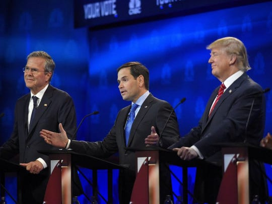 Marco Rubio, center, speaks as Jeb Bush, left, and Donald Trump react.