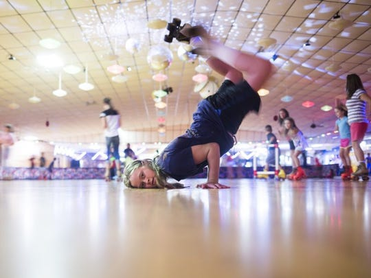 Makayla Wheatley, 12, of Anderson does a head stand in the middle of the rink at Skateland USA.