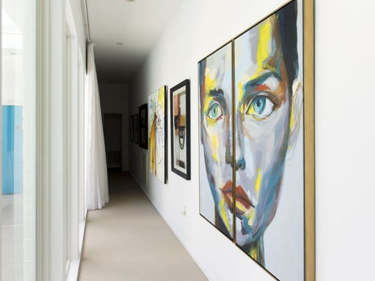 The gallery wall runs along the hallway to the master suite, opposite the glass doors leading to the pool. Paula says, 'I love art. I could spend all my money on art.'
