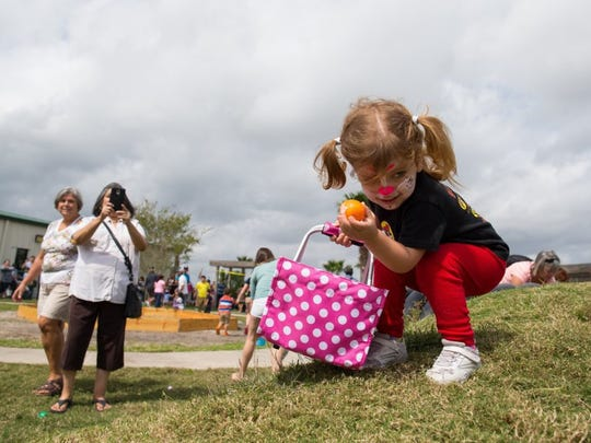 COURTNEY SACCO/CALLER-TIMES Two-year-old Lindsey Fearn picks up a plastic egg during an egg hunt Saturday, March 26, 2016, at the Fellowship of Oso Creek's 16th Annual Easter Festival.