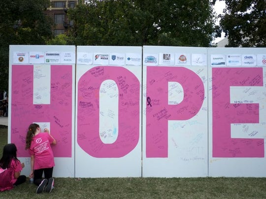 Grace Magulies, 11, signs the name of her grandmother, Lola Grace, who's a cancer victim, alongside her friend Lily Baker, 10, who signed the name of her mom, Jessica Baker, who's a cancer survivor, during the American Cancer Society Making Strides Against Breast Cancer walk at the World's Fair Park on Oct. 2, 2016.