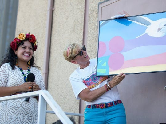 COURTNEY SACCO/CALLER-TIMES Artist Sandra Gonzalez presents Caller-Times President Libby Averyt with an extra panel from the mural 'Endless Sunset: The Colors of Our City' during its dedication Friday, Aug. 5, 2016.