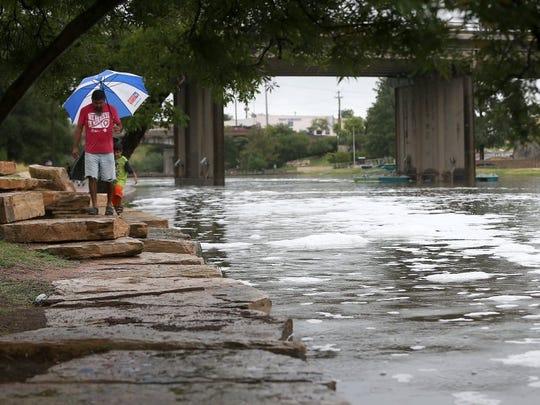 San Angelo residents walk along the Concho River.