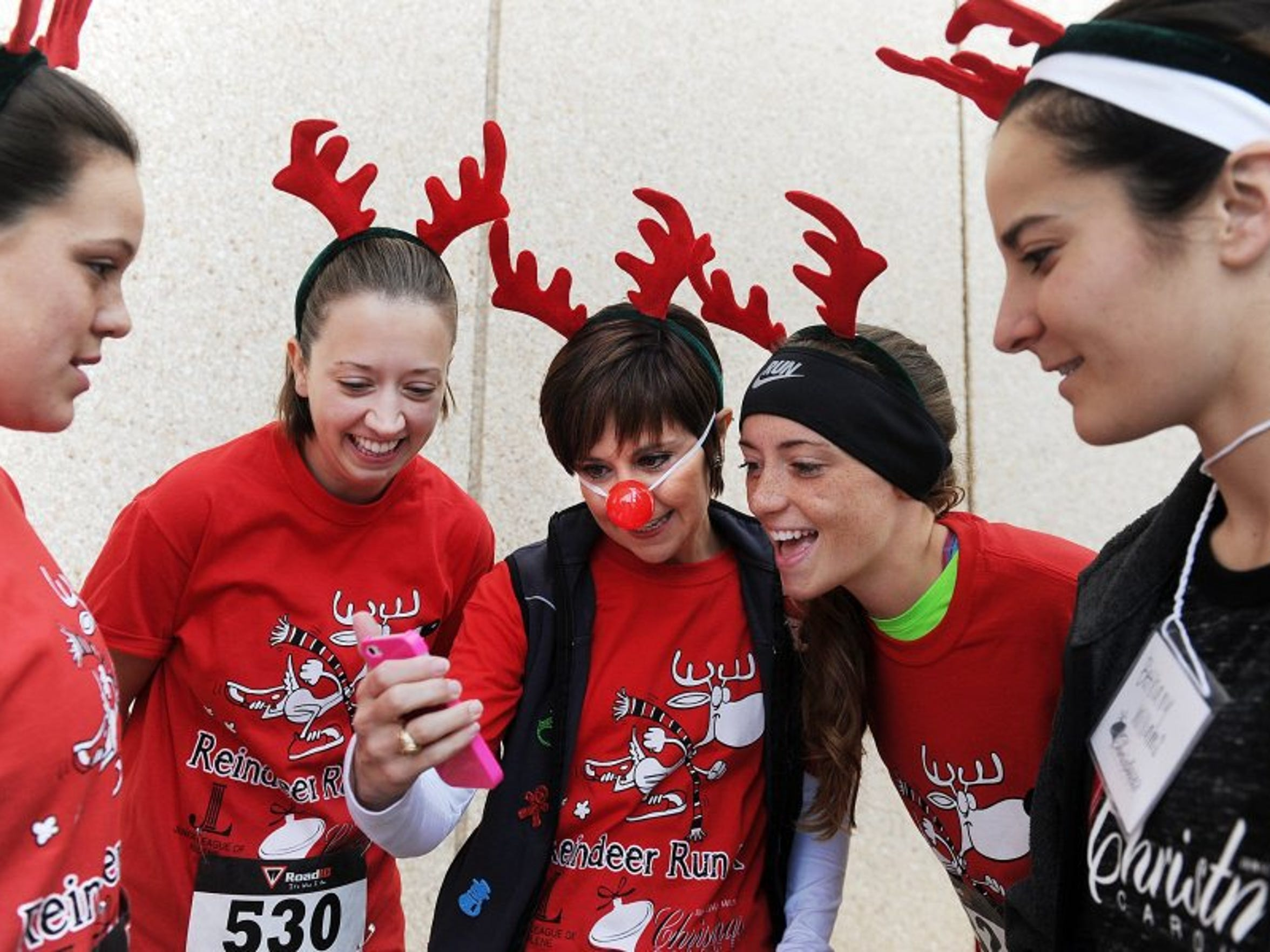 Reindeer Run participants from left, Hailey Presley, Megan Baldree, Vanessa Bryan, Holiday Williams and Bethany Williams check a group picture before starting their 5-kilometer run organized by Junior League of Abilene in 2014.