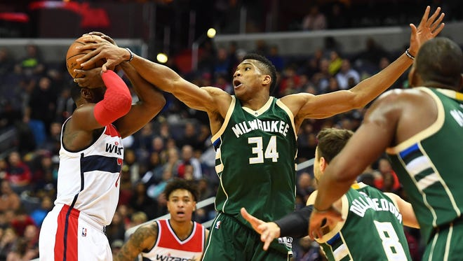 Giannis Antetokounmpo blocks a shot attempt by Wizards guard John Wall.