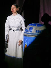 """Princess Leia (Maria Leonetti), hair buns and all, takes the stage with R2D2 during a rehearsal for the Bootless Stageworks production of """"Star Wars: A New Musical Hope."""""""