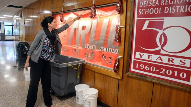 Jessica Ippolito, a teacher at Delsea Regional High School, describes how water flowed through a display case after heavy rain flooded sections of the building in September 2014.