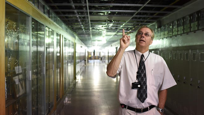 Wayne Weaver, Vineland Public Schools Executive Director of Physical Properties stands in hallway and points at the work of new pipes that were installed at the Vineland High School , South building. August 19, 2015. Staff photo/Craig Matthews