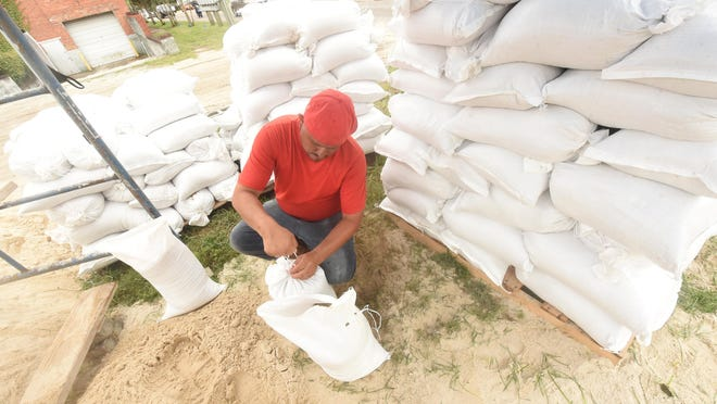 Patricio Dominguez ties up sandbags for sale off Front Street just before the Cape Fear Memorial Bridge in Wilmington, N.C., Monday as Tropical Storm Isaias moves towards North Carolina.