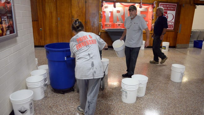 June Waldron (left), and Paul Montalto (center) work in Delsea Regional High School's lobby after heavy rainfall flooded sections of the building on Thursday.