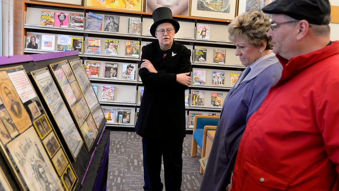 Rick Brown wears a stovepipe hat and black suit as he talks about his Traveling Lincoln Assassination Museum on display at the East Lansing Public Library with Stephanie and David Skeels Wednesday. Brown said he has collected history on the Lincoln assassination for 50 years.