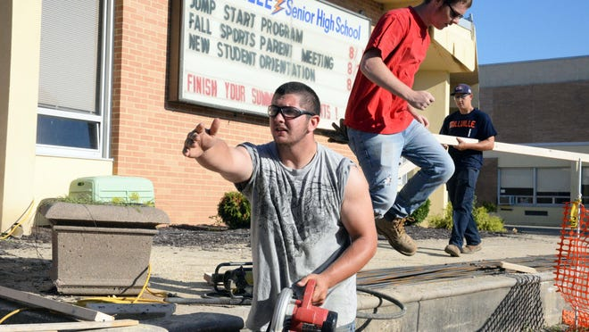 Millville High School graduates Tyler Klawitter,18 (center), and Harry Montero, 18 (right), and current student Justin Woolbert, 16, help with a construction project at the school on Thursday. The Millville School Distirct has employed the young men to help subcontractor Gifford Concrete build a new landing, sidewalks and steps to the main entrance of the 50-year-old school this summer.