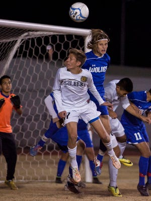 Junior Carter Rumsey (R), 1, of the Chandler Wolves assists the goal keeper and blocks the ball from 17, Danny Baca (C) and the Gilbert Tigers Friday January 16, 2014 in Gilbert, Ariz. Scoring the only two goals of the game, the Tigers would go on to defeat the Wolves, 2-0.
