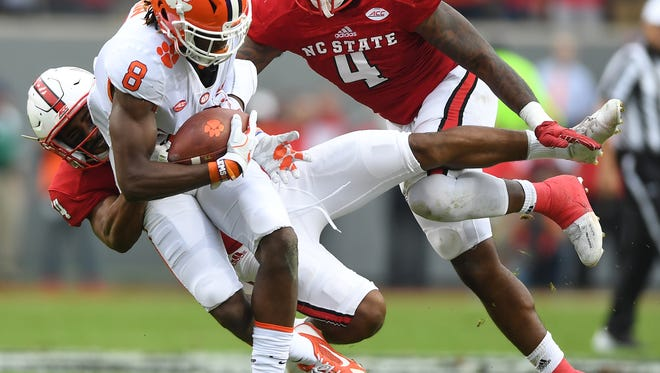 Clemson wide receiver Deon Cain (8) is brought down by NC State safety Tim Kidd-Glass (34) after first down reception during the 2nd quarter on Saturday, Nov. 28, 2017 at Clemson's Memorial Stadium.