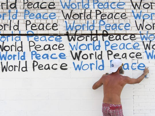 "Renda Writer creates for a part of his World Peace Mural Tour at a building on the corner of Grand River and Rosa Parks Blvd. in Detroit. ""I just think it's what we need,"" said Writer, referring to the mural's message."