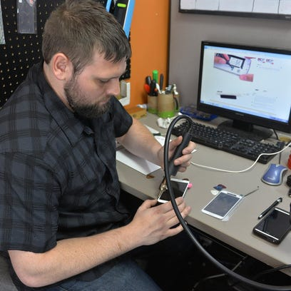 Josh Nelson, owner of LGS Electronics in St. Cloud, shows two LG phones Wednesday at his store. One had a new screen installed, and the other has a cracked screen. Nelson said summer heat, humidity and water are common causes of phone damage.