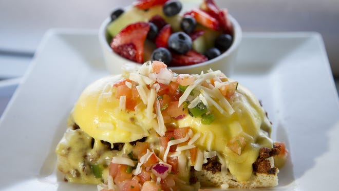 Chorizo Benedict served with a side of fruit from Sunnyside Breakfast Lounge in Mesa on July 10, 2015. The poached eggs are placed over spicy chorizo and grilled focaccia bread and topped with hollandaise, pico de gallo and pepper-jack cheese.