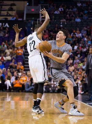 The Suns' Devin Booker (1) tries to spin away from the Nets' Markel Brown (22) in the first half at Talking Stick Resort Arena in Phoenix, Ariz. on Thursday, February 25, 2016.