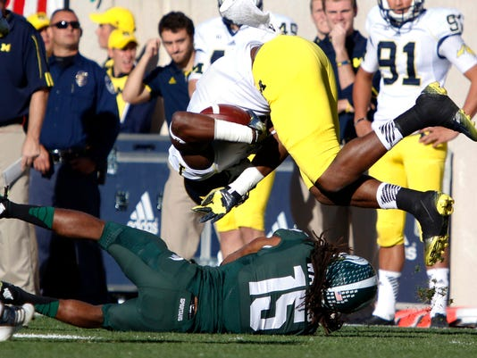 Michigan receiver Devin Funchess, top, is upended by Michigan State's Trae Waynes during the second quarter of an NCAA college football game, Saturday, Oct. 25, 2014, in East Lansing, Mich. (AP Photo/Al Goldis)