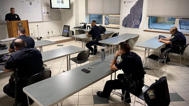 Fall River police officers stay at least six feet apart from one another during a recent roll call briefing before heading out on patrol.