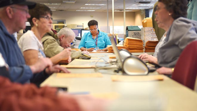 Denise Tucker, center, mails out absentee ballots during early voting at the Minnehaha County Courthouse Tuesday, April 24, in Sioux Falls.