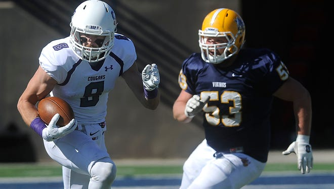 USF's #8 Josh Angulo runs down the field against Augustana's #53 Jake Lee during football action at Kirkeby-Over Stadium in Sioux Falls, S.D., Saturday, Oct. 11, 2014.
