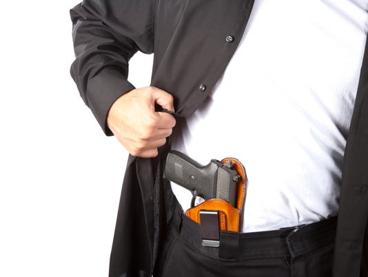 A man showing his concealed gun