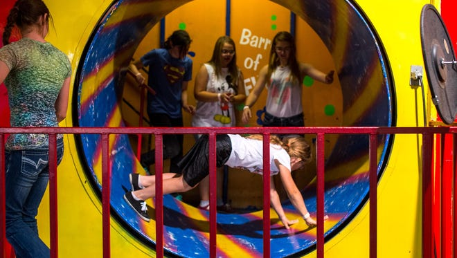 Sam Faulkner crawls in the Barrel of Fun, a spinning exit to one of the fun houses on the midway at the 2015 Montana State Fair.