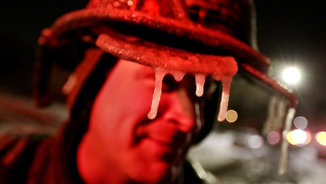 Detroit firefighter Dan Schaecher, 40, is covered in ice after fighting a fire at a two-family flat on Monica on Detroit's west side on Monday. Single-digit temps and windchills in the negative teens make the work of firefighters difficult, freezing fire hydrants.