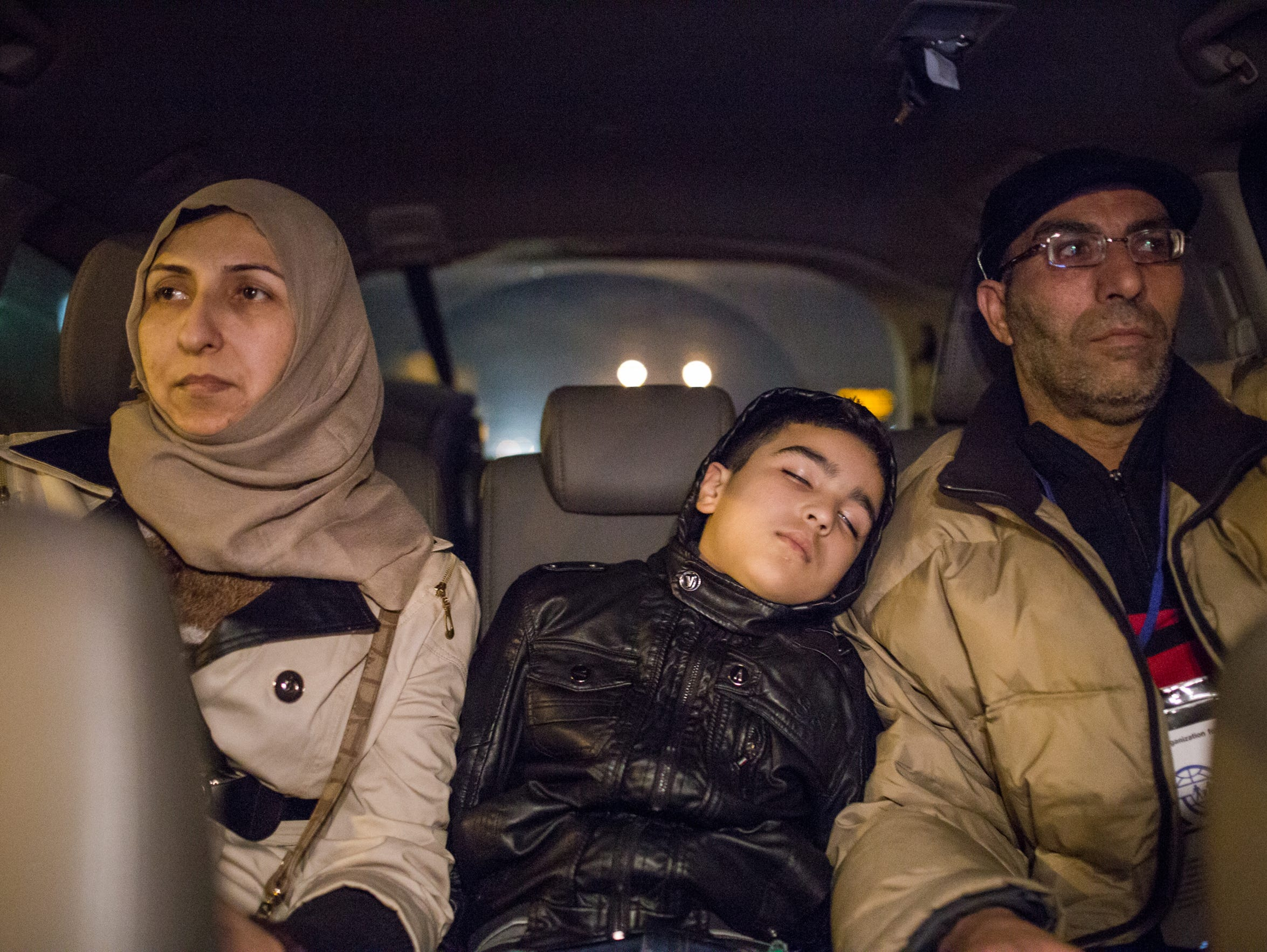 Arab Buteh, 8, falls asleep sitting between his parents