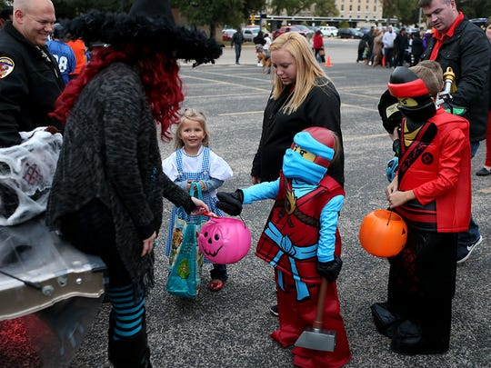 Trick-or-treaters hold out their buckets for candy during the Tom Green County Sheriff's Office's second annual Halloween Trunk or Treat Tuesday, Oct. 31, 2017.