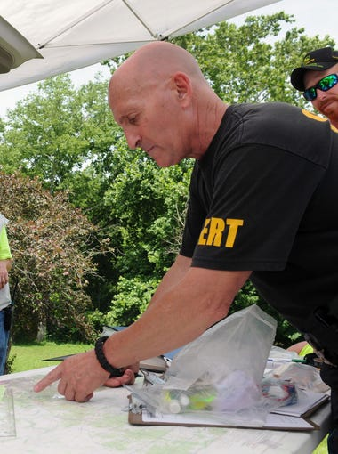 Joe Minney points out the area they are searching on a map Monday, June 22, 2015, at a command station set up off of U.S. 50. The body of Tiffany Sayre was found Saturday night off of Cave Road.