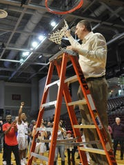 Shippensburg University men's basketball coach Chris Fite pulls down the championship net after the Raiders won the PSAC title, 73-63 over Kutztown.