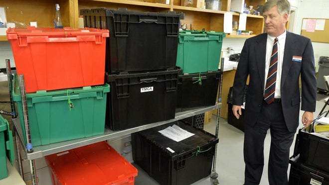 Chairman Thomas Mahoney looks at boxes of ballots yet to be counted at the Board of Elections office in June 2020.