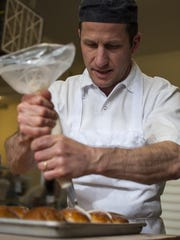 Pastry chef Jeremy Gullen puts icing on freshly-baked