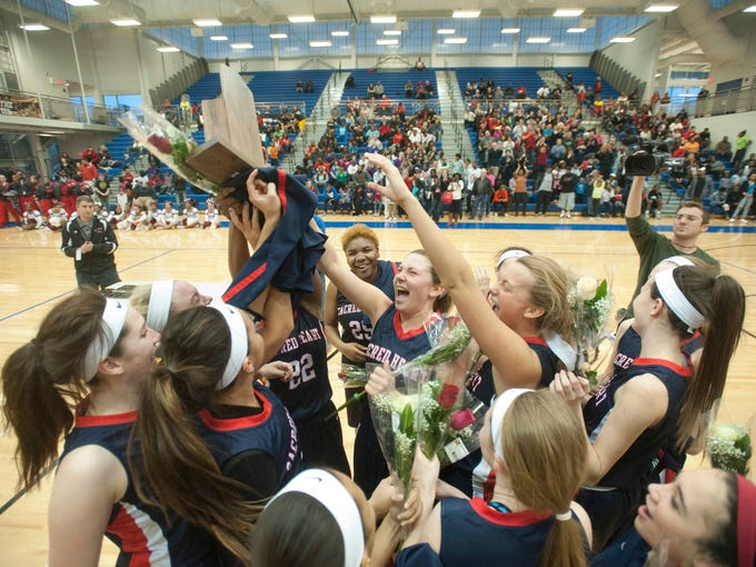 Sacred Heart hoists their championship trophy after defeating Ballard 46-39 in the Kentucky 7th Regional Girls Basketball Championship. March 07, 2014