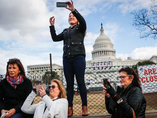 Micaela Johnson, of Leewood, Kan., in town to take part in Saturday's Women's March on Washington, takes a selfie with the Capitol in the background as preparations continued on Jan. 18, 2017, for the inauguration.
