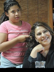 Samantha Garcia, 11, fixes her mother's hair. Her mother,