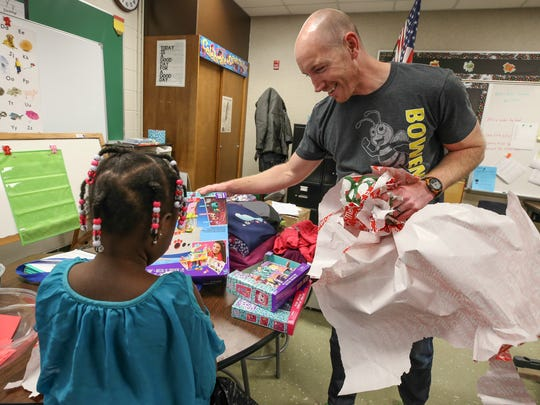 Family Resource Center coordinator Justin DeLorenzo helps to unwrap presents with a student during a party that was put on at Bowen Elementary School with help from LMPD's 8th Division.