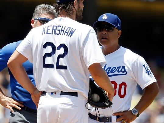 Los Angeles Dodgers starting pitcher Clayton Kershaw, center, talks with manager Dave Roberts, right, and trainer Nathan Lucero during the second inning of a baseball game against the Atlanta Braves in Los Angeles, Sunday, July 23, 2017. Kershaw continued to pitch and complete the second inning, but did not return for the third inning. (AP Photo/Alex Gallardo)