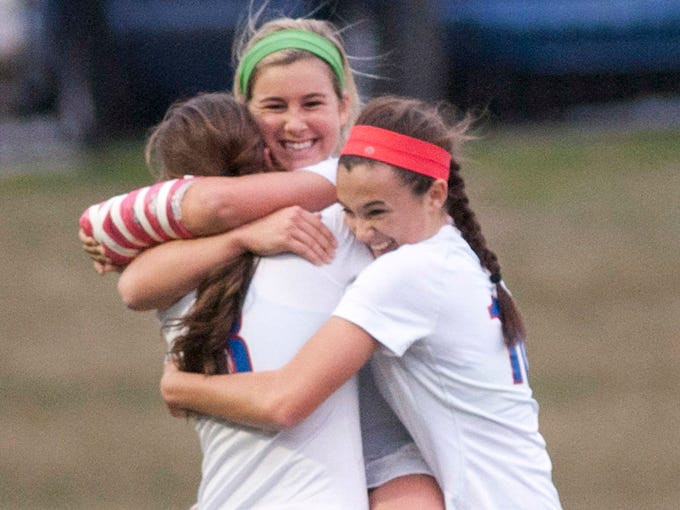 Christian Academy of Louisville's Kenzie Dannelly, top center, is hugges by teammates  Lindsey Dunn, left, and  Megan Mintman, right, after Dannely scores. The goal was enough to defeat Manual, 1-0. Oct. 22, 2013