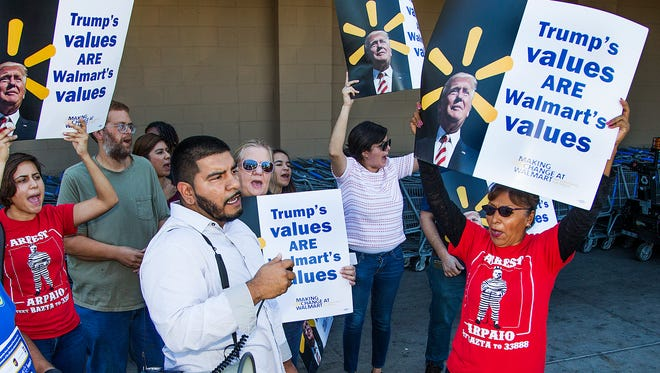 Tomas Robles, Phoenix, a Democrat and executive director of Living United for Change in Arizona, with megaphone, chants with other protesters at anti-Trump and anti-Walmart rally outside the Walmart at 3721 E. Thomas Road in Phoenix, Wednesday, October 26, 2016.