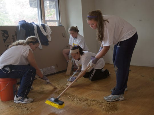 Eatontown - Monmouth University Softball team members Kayla Weisere, Nikki Sandlier, Christine Scherr, and Lauren Saal work on removing old finish from livingroom floors.  Volunteers from a variety of groups, including the Asbury Park Press, pitched in during Make A Difference Day to work on the Rose Court Group Home Renovation Project in Eatontown, doing yard work, scrapping down the old wood floors, painting and more. Peter Ackerman/Staff Photographer - difference121027a